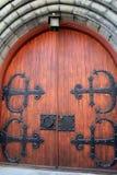 Detalhe lindo em portas de madeira pesadas com preto elaborado, hardware do metal fotos de stock