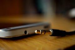 Detalhe macro de um jaque do fones de ouvido do metal próximo o conector no telefone celular, na superfície de madeira Imagens de Stock