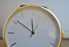 Detalhe macro de um relógio de pulso dourado luxuoso com um seletor branco no fundo de madeira como um símbolo de e um relógio ca Fotografia de Stock Royalty Free