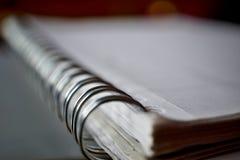 Detalhe macro de uma espiral obrigatória do metal do bloco de notas branco na superfície de prata Imagens de Stock