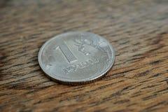 Detalhe macro de uma moeda de prata brilhante de uns rublo & x28; Rouble& x29; como o símbolo da moeda do russo no fundo de madei Foto de Stock Royalty Free