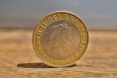 Detalhe macro de uma moeda de prata e dourada com cabeça da rainha em um valor de duas libras britânicas 2 de GBP na superfície d foto de stock