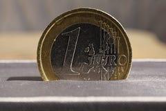 Detalhe macro de uma moeda do Euro da prata e do ouro colocada na caixa de presente luxuoso cinzenta da joia Imagens de Stock Royalty Free