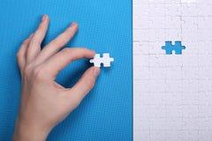 Detalhes brancos de um enigma em um fundo azul Um enigma é um plutônio Imagem de Stock