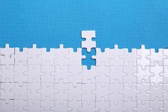 Detalhes brancos de um enigma em um fundo azul Um enigma é um plutônio Imagem de Stock Royalty Free