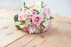 Detalhes da manhã do dia do casamento duas alianças de casamento do ouro estão na tabela de madeira marrom Imagens de Stock Royalty Free