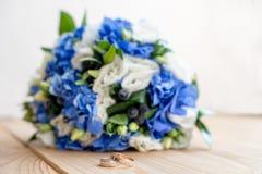 Detalhes da manhã do dia do casamento duas alianças de casamento do ouro estão na tabela de madeira marrom Imagem de Stock
