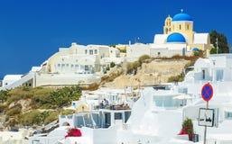 Detalhes de arquitetura das casas e dos hotéis brancos com os turistas nas salas contra as rochas, Santorini, Grécia fotos de stock