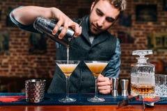 detalhes de empregado de bar que derramam bebidas alcoólicas extravagantes no partido Imagens de Stock