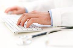 Detalhes de mãos do doutor que datilografam no teclado Imagens de Stock Royalty Free