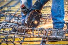 Detalhes de trabalhador do coordenador de construção que corta as barras de aço e o aço reforçado no terreno de construção fotografia de stock