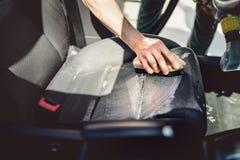 Detalhes do conceito dos cuidados com o carro, do detalhe e da limpeza Trabalhador que usa o techonology de limpeza para o estofa foto de stock royalty free