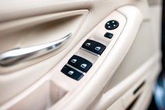 Detalhes interiores de couro do carro de puxador da porta com controle das janelas fotos de stock