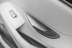 Detalhes interiores do couro branco do carro de puxador da porta com controles e ajustes das janelas Controles da janela de carro fotografia de stock royalty free