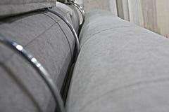 Detalj av baksidan och nackstöden av den gråa veloursoffan royaltyfri fotografi