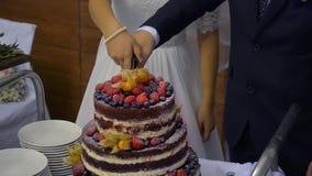 Detalj av bröllopstårtaklipp av nygifta personer lager videofilmer