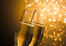 Detalj av champagneflöjter med guld- bubblor på mörk guld- ljus bokehbakgrund Royaltyfria Bilder