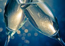 Detalj av champagneflöjter med guld- bubblor på blå ljus bokehbakgrund Arkivbild
