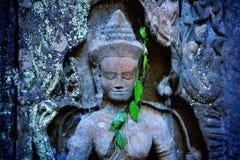 Detalj av den forntida statyn som snider den Apsara dansaren i Cambodja med gröna sidor royaltyfria foton