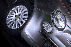 Detalj av den främre billyktan och däcket av en bil Arkivbild