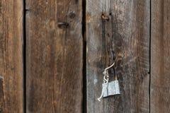 Detalj av den gamla dörren av ladugården med den öppna hänglåset som som hänger på konsolen, tappningbakgrund Royaltyfri Bild