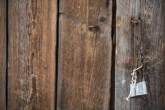 Detalj av den gamla dörren av ladugården med den öppna hänglåset som som hänger på konsolen, tappningbakgrund Royaltyfria Bilder