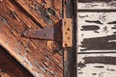 Detalj av den gamla dörren och det rostade gångjärnet Arkivbilder