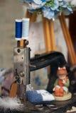Detalj av den gamla symaskinen, sax och tappningrullar av tråden Handgjord nåldyna royaltyfri foto