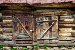 Detalj av den gamla trätexturerade och red ut ladugårddörren arkivbilder