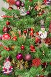 Detalj av den gröna julgranen med kulöra prydnader, jordklot, stjärnor, Santa Claus, snögubbe, röda kängor, skor, stearinljus Arkivfoto