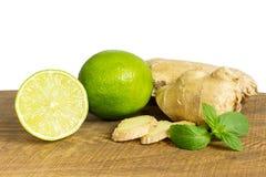 Detalj av den hel och för snitt nya ingefäran med limefrukt arkivbilder