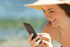 Detalj av den lyckliga turisten som använder telefonen på stranden arkivbild
