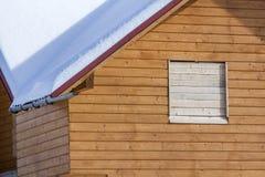 Detalj av den nya träekologiska traditionella stugan av naturliga bråtematerial med det branta taket som täckas med snö på solig  royaltyfri foto