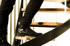 Detalj av den svarta mockaskinnkängan och svart jeans som bär mannen som klättrar den inre trappuppgången Inbrottbegrepp royaltyfria foton