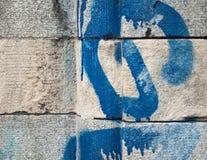 Detalj av den texturerade stenhuggeriarbetet med blåa grafitti Royaltyfria Bilder