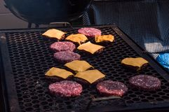 Detalj av det bärbara mässingsgallret av kocken Grilla hamburgare och ostburgare med bränningkol BCoqueiro arkivbild