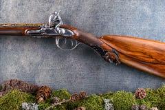 Detalj av det gamla antika långa vapnet med skogstilleben på grå bakgrund, historiska vapen Royaltyfri Foto