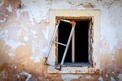 Detalj av det gamla skadade fönstret och den texturerade spruckna väggen Arkivbild