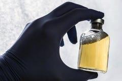 Detalj av det medicinska innehavet för hand en liten medicinflaska, begreppsmässig bild Royaltyfri Fotografi
