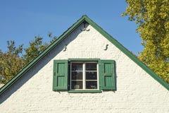 Detalj av det tyska fönstret för hus` s med vit fasad och blå himmel b Arkivfoto