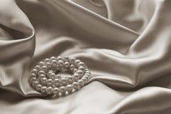Detalj av draperat beige siden- tyg med pärlan arkivbilder