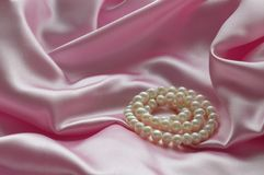 Detalj av draperat rosa siden- tyg med pärlor arkivbilder