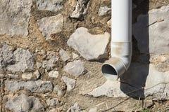 Detalj av en avloppsränna och en stenvägg från ett landshus i katt Arkivbild