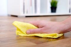 Detalj av en hand med golvet för svamplokalvårdparkett royaltyfri foto
