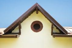 Detalj av en lantlig byggnad med ett runt fönster royaltyfri bild