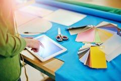 Detalj av en modeformgivare som arbetar med minnestavlan arkivfoto