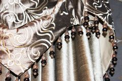 Detalj av en rå siden- gardin för taupe med pärlor arkivfoton