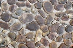 Detalj av en vägg som göras av flodstenar, stenbakgrund, vägg, trottoar Arkivbilder