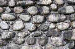 Detalj av en vägg som göras av flodstenar, stenbakgrund, väggen, trottoar, grå färger och bruna mörka färger Arkivfoto