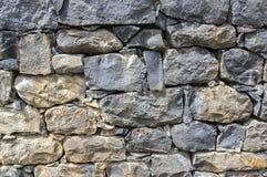 Detalj av en vägg som göras av stenar, stenbakgrund, väggen, trottoar, grå färger och bruna mörka färger Arkivbilder